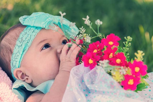 bebe feliz segurando uma flor
